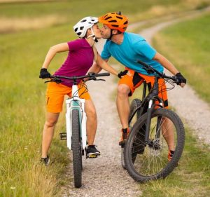 couple on electric mountain bikes standing on gravel road between grass outdoors in summer in rural landscape kissing